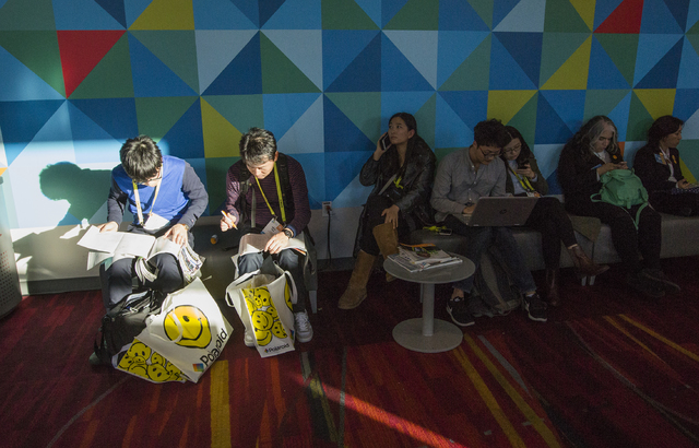 A beam of light shines on people taking a break during CES 2017 at the Las Vegas Convention Center on Thursday, Jan. 05, 2017. Around 175,000 people are expected the attend the world's largest con ...