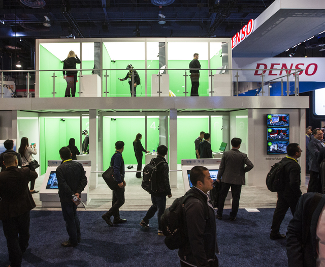People walk passed the auto supplier DENSO booth during CES 2017 at the Las Vegas Convention Center on Thursday, Jan. 05, 2017. Around 175,000 people are expected the attend the world's largest co ...