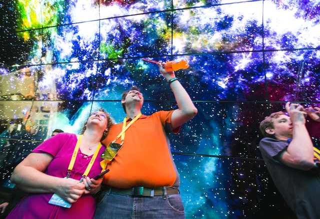 Cynthia Robinson, left, and Timothy Mason view a wall of LG OLED 4K panels during CES 2017 at the Las Vegas Convention Center on Thursday, Jan. 05, 2017. Around 175,000 people are expected the att ...