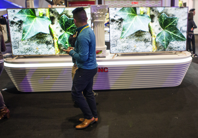 A man walks past the D-LED TV's at the CNC booth during CES 2017 at the Las Vegas Convention Center on Thursday, Jan. 05, 2017. Around 175,000 people are expected the attend the world's largest co ...