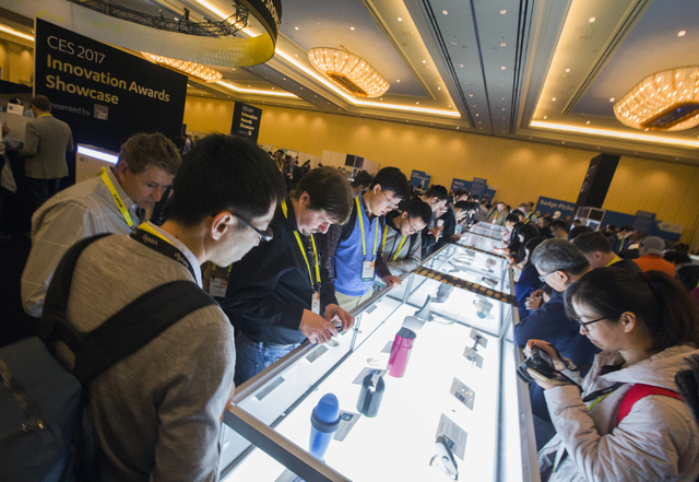 People gather around the latest tech gadgets in the Innovation Awards Showcase Thursday, Jan. 05, 2017, at the Venetian Ballroom during CES 2017. Around 175,000 people are expected the attend the  ...