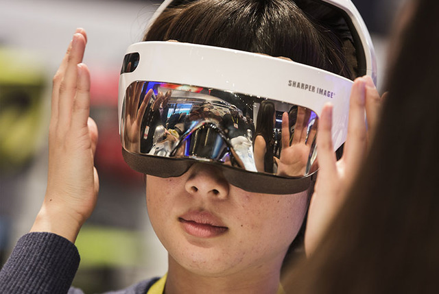 Hyunji Son tries a ocular massager at Sharper Image during CES 2017 in the Las Vegas Convention Center on Friday, Jan. 06, 2017. Around 175,000 people are expected the attend the world's largest c ...