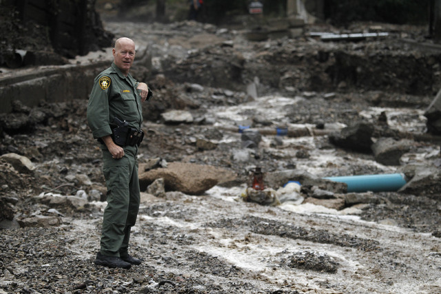 Las Vegas Metropolitan police officer William Corder stands on what was Rainbow Canyon Road in the Rainbow Subdivision on Mount Charleston on Monday, July 28, 2014.  (Justin Yurkanin/Las Vegas Rev ...