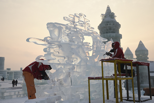 Contestants carve an ice sculpture during an international ice sculpture contest during the Harbin Ice and Snow festival in Harbin, capital of northeast China's Heilongjiang Province. The city of  ...