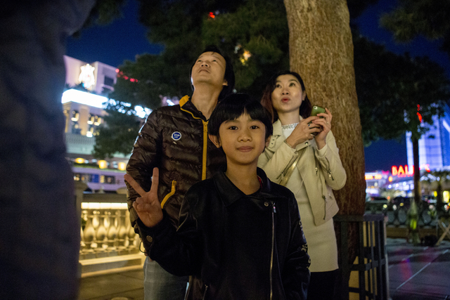 Feng Guan, left, May Wu, right, and their son Timmy  Guan, tourists from China, watch the fountain show in front of the  Bellagio in Las Vegas, Tuesday, Nov. 29, 2016, in downtown Las Vegas. (Eliz ...