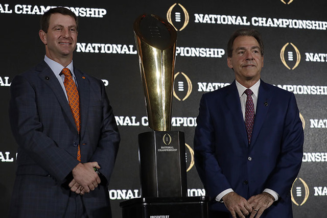 Clemson head coach Dabo Swinney and Alabama head coach Nick Saban pose with the championship trophy during a news conference for the NCAA college football playoff championship game Sunday, Jan. 8, ...