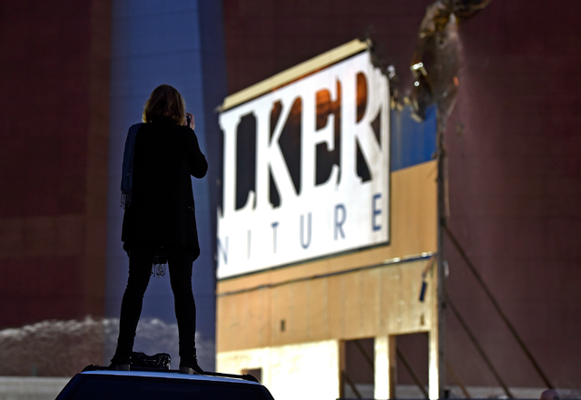Walker Furniture co-owner Linda Alterwitz-Mizrahi photographs the final section of the Walker Furniture warehouse being torn down Monday, April 11, 2016, in Las Vegas. The building had to be remov ...