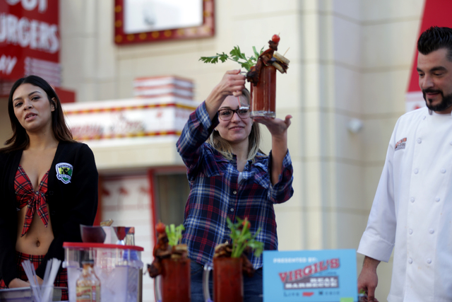 Claudia Durenberger holds up a bloody mary next to Tara Hough and Executive Sous Chef Abe Tsavalakoglou at the inaugural National Hangover Day Cocktail Competition at the LINQ Promenade on Sunday, ...