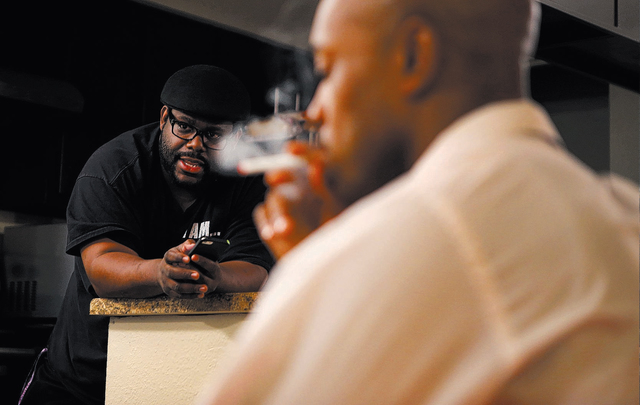 """Director Torrey Russell, 43, speaks to an actor as actor Mario Peoples, 33, smokes an electronic cigarette prop after rehearsing for the play """"The Mountaintop"""" at Russell's apart ..."""