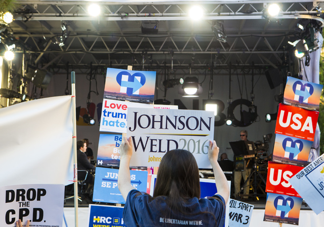 A supporter of Libertarian presidential candidate Gary Johnson holds up a sign in front of the MSNBC stage ahead of the third presidential debate at UNLV in Las Vegas, on Wednesday, Oct. 19, 2016. ...