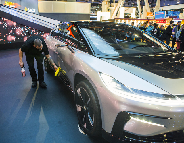 A man wipe down Faraday Future's new concept car during CES 2017 in the Las Vegas Convention Center on Friday, Jan. 06, 2017. Around 175,000 people are expected the attend the world's largest cons ...