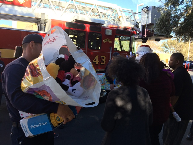 Firefighters deliver presents Jan. 9, 2016, to a family staying at La Quinta Inn & Suites. The family had their home destroyed Dec14 by a devastating fire. Operation Fire Holiday Emergency Ass ...