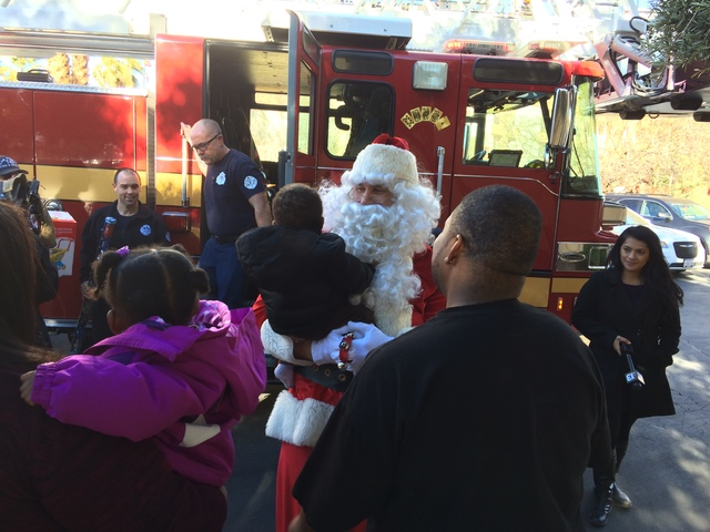 Santa holds the Cole family's infant son soon after the firetruck bringing replacement Christmas gifts arrived Jan. 9, 2016, at La Quinta Inn & Suites, where the Cole family is staying after ...