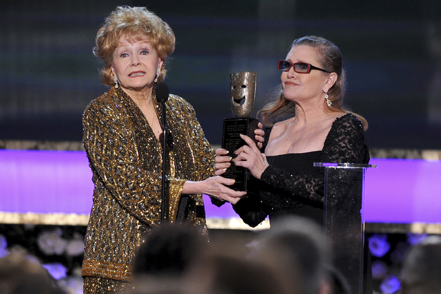 In this Jan. 25, 2015, file photo, Carrie Fisher, right, presents her mother Debbie Reynolds with the Screen Actors Guild life achievement award at the 21st annual Screen Actors Guild Awards at th ...