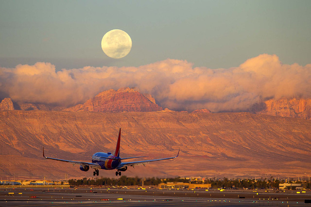 A Southwest airliner makes its descend onto the McCarren International Airport tarmac early morning on Sunday, Oct. 16, 2016, as a nearly full moon, prepares to set behind the Spring Mountains. Ri ...