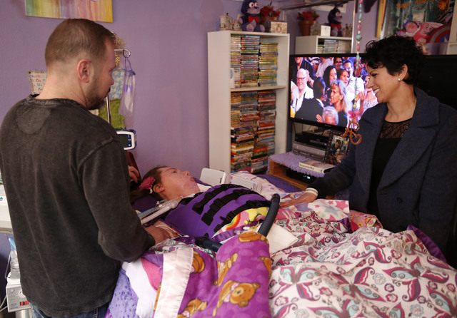 Brandon Gardner speaks with Make-A-Wish Southern Nevada CEO Caroline Ciocca at his daughter Allie's bedside at the Gardner family home, Thursday, Jan. 12, 2017 in Las Vegas. Make-A-Wish Southern N ...