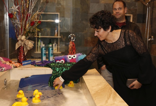 Make-A-Wish Southern Nevada CEO Caroline Ciocca places a rubber duck in the newly installed bathtub at the Gardner family home, Thursday, Jan. 12, 2017, in Las Vegas. Make-A-Wish Southern Nevada a ...