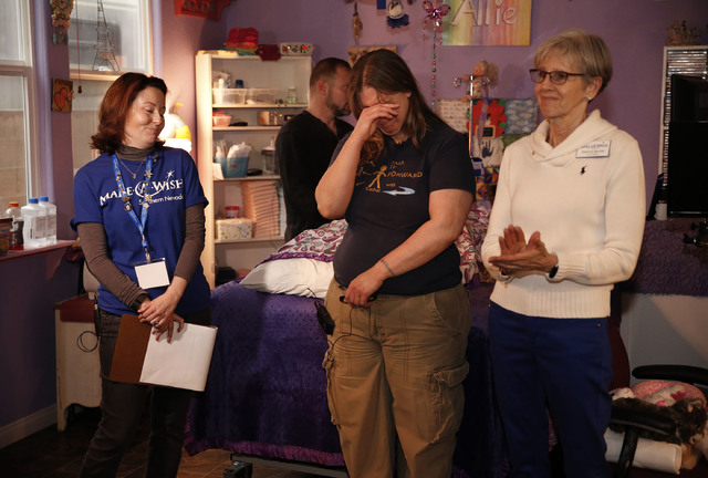 Sandy Gardner, center, is brought to tears after Make-A-Wish Southern Nevada and its partners formally revealed the Gardner family's long-awaited bathroom makeover, including a custom tub, at the  ...