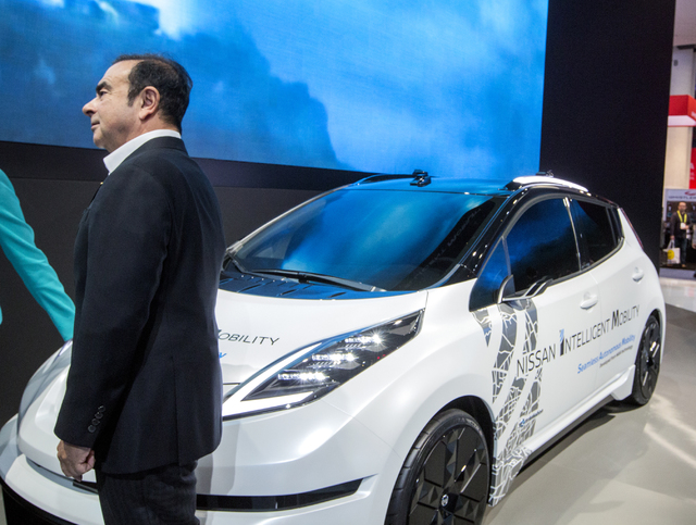 Carlos Ghosen, chairman and CEO of Nissan, stands beside a LEAF electric car with Nissan Intelligent Mobility during CES 2017 at the Las Vegas Convention Center on Thursday, Jan. 05, 2017. Around  ...