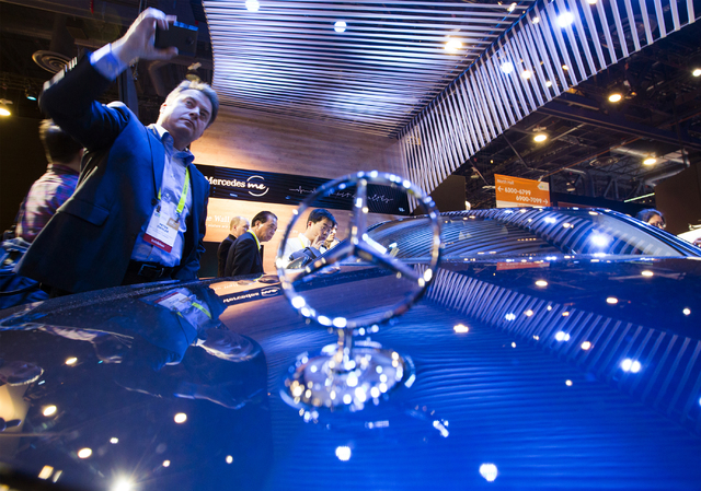 People views a S500 model with the latest technology in the Mercedes Benz booth during CES 2017 at the Las Vegas Convention Center on Thursday, Jan. 05, 2017. Around 175,000 people are expected th ...