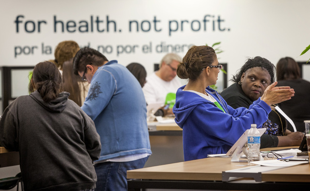 Glynis Brooks-Groom, right, listens while health advocate Lorie Struebing explains health plans at Nevada Health CO-OP, 3900 Meadows Lane, on Monday afternoon, March 31, 2014. The local office was ...