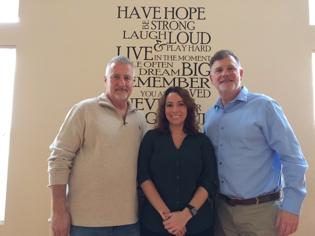 Steve Appel, left, Dennis Hofmaier, center, and Veronica Scala stand before a saying on the wall of the southwest home where those recovering from addiction. Higher Path Living seeks to help those ...