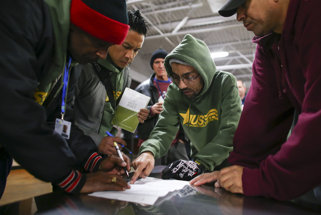 Giovanni Lomagno, outreach coordinator at U.S. Vets, center right, helps prepare before the start of the Southern Nevada Homeless Census at Catholic Charities in downtown Las Vegas on Tuesday, Jan ...