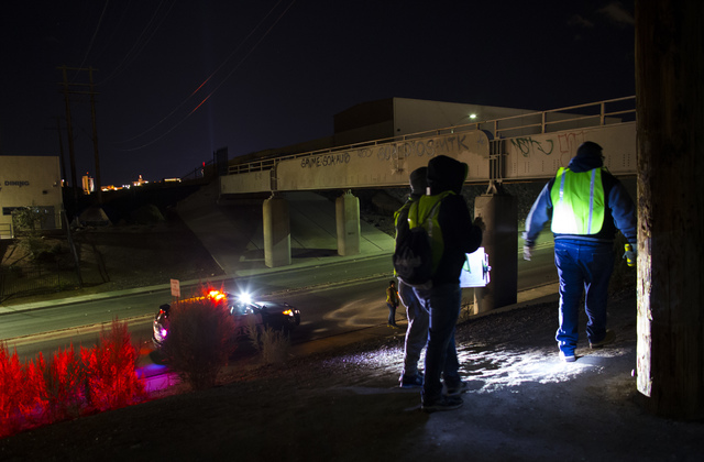 Volunteers and Las Vegas police search for homeless people around an underpass along Owens Avenue during the Southern Nevada Homeless Census in downtown Las Vegas on Tuesday, Jan. 24, 2017. (Chase ...