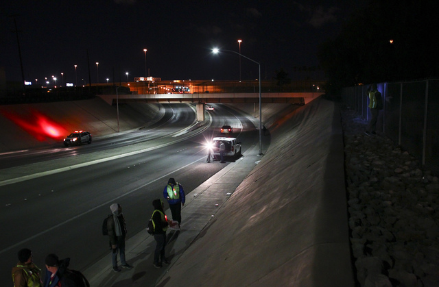 Volunteers and Las Vegas police search for homeless people near an underpass along Washington Avenue during the Southern Nevada Homeless Census in downtown Las Vegas on Tuesday, Jan. 24, 2017. (Ch ...