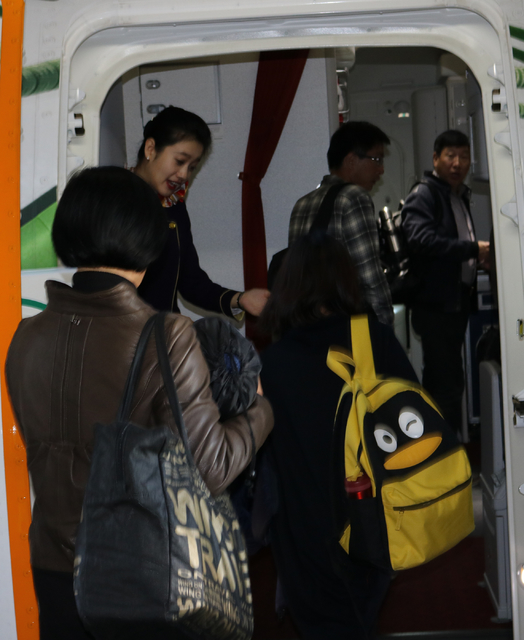 Passengers of the inaugural Hainan Airlines flight from Beijing to Las Vegas board the airplane at Beijing International Airport Friday, Dec. 2, 2016. Las Vegas tourism officials are hoping for a  ...