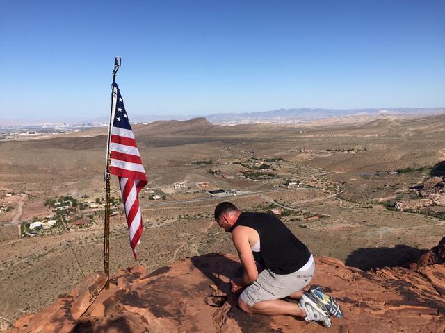 Homeless Marine veteran Matt Shepard kneels by a U.S. flag June 3, 2015 near Red Rock Canyon National Conservation Area. (Courtesy Matt Shepard)