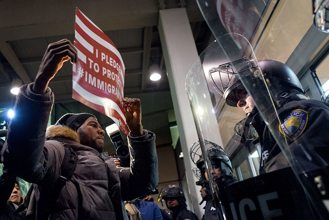 A protester stands facing police officers at an entrance of Terminal 4 at John F. Kennedy International Airport in New York, Saturday, Jan. 28, 2017,  after earlier in the day two Iraqi refugees w ...