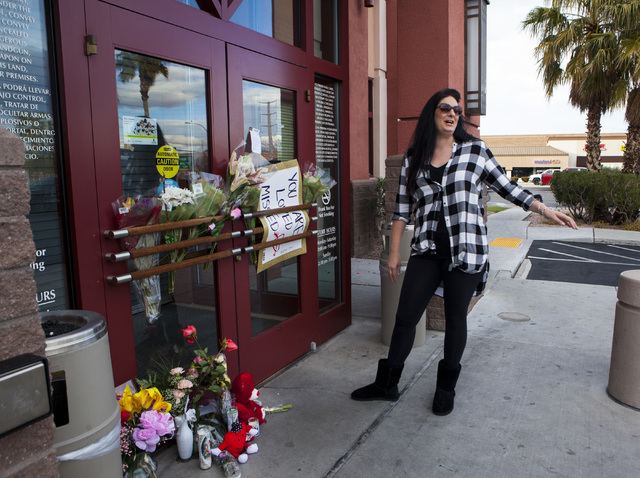 Michelle Zimkus lays out flowers in front of Jared, a jewelry store where employee Kimberlee Ann Kincaid-Hill died after being accidentally shot by a security guard during an armed robbery at the  ...