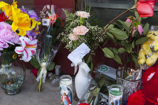 Flowers sit in front of Jared, a jewelry store where employee Kimberlee Ann Kincaid-Hill died after being accidentally shot by a security guard during an armed robbery at the store in Henderson on ...