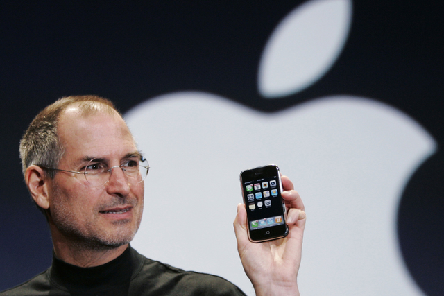 "Apple CEO Steve Jobs holds up an iPhone Jan. 9, 2007, at the MacWorld Conference in San Francisco. Jobs' ""magical product"" reshaped culture, shook up industries and made it seem possible to do jus ..."