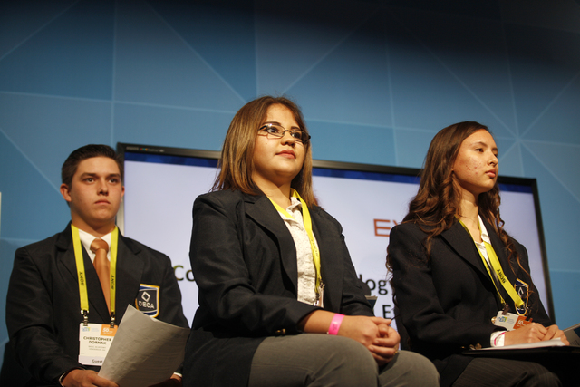 """Students Christopher """"CJ"""" Dornak, Guadalupe Torres, and Clarissa Neff sit on stage before delivering their pitches at the Consumer Technology Association Student Business Pitch C ..."""