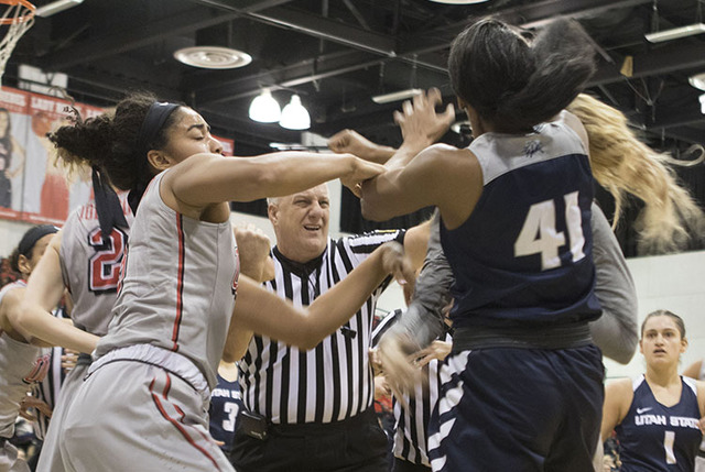 Paris Strawther (left) attempts to stop a fight between Aggies Antoina Robinson and Lady Rebels Katie Powell during the third quarter of their game at the Cox Pavilion on Jan. 7, 2017. (Heidi Fang ...
