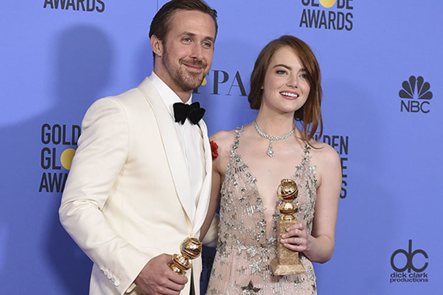 """Ryan Gosling, left, and Emma Stone pose in the press room with the award for best performance by an actor and actress in a motion picture - musical or comedy for """"La La Land"""" at  ..."""