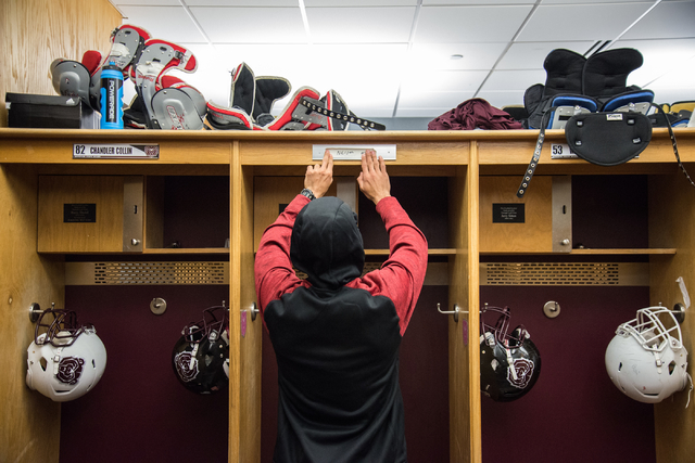 Rickey Nichols, cousin and roommate of fallen Missouri State football player Richard Nelson, places tape with Nelson's name over a vacancy sign after removing Nelson's nameplate from above the loc ...