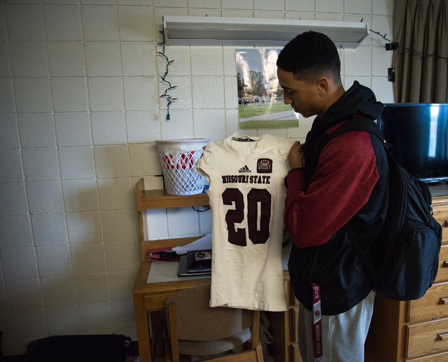 Rickey Nichols, cousin and roommate of fallen Missouri State football player Richard Nelson, shows Nelson's jersey in their dorm room on campus in Springfield on Tuesday, Jan. 17, 2016. (Ryan Welc ...