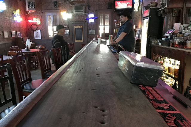 Legendary cigar-burn marks, foreground, pock the Pioneer Saloon's cherrywood bar in Goodsprings Thursday, Jan. 12, 2017, that bartender Chad Hanson (background right) says were left by actor Clark ...