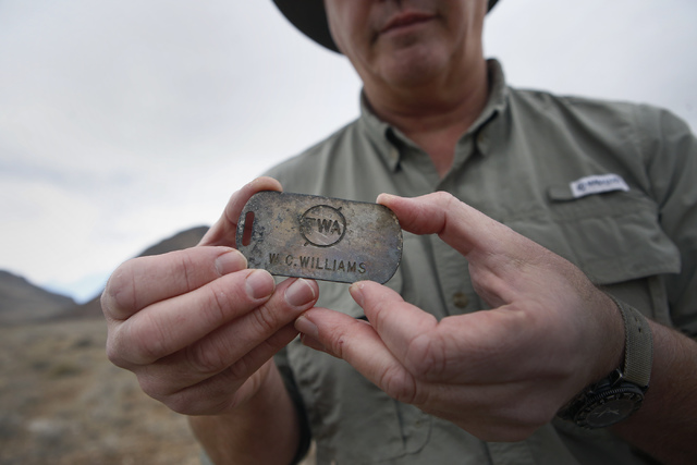FAA accident investigator Mike McComb, 50, holds a crew baggage tag which was the property of Wayne C. Williams, who was the pilot in command during the 1942 DC-3 crash that killed actress Carole  ...