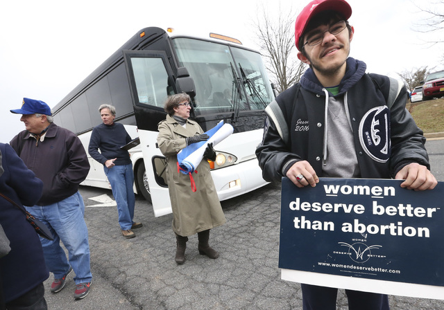 Jesse Davis  holds a sign as he prepares to board a bus at Sacred Heart of Jesus Catholic Church in Winchester, Va., to travel to Washington for the March for Life rally,  Friday, Jan. 27, 2017. ( ...