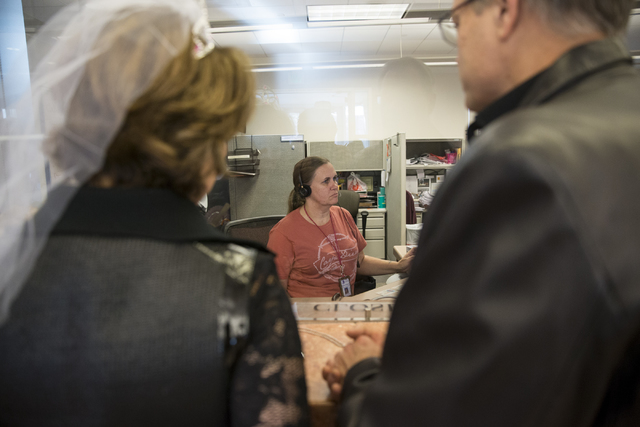 Office specialist Karen Stuart, center, assists Nancy Fromm and Karl Bode of Phoenix with their marriage license at the Clark County Marriage License Bureau on Friday, Jan. 13, 2017, in Las Vegas. ...