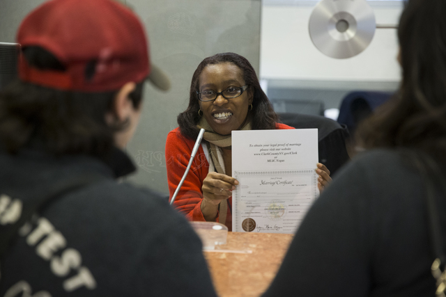 Office specialist Samadhia Williams, center, assists Adriana Minacapilli and Greta Guilbault of Rhode Island with their marriage license at the Clark County Marriage License Bureau on Friday, Jan. ...