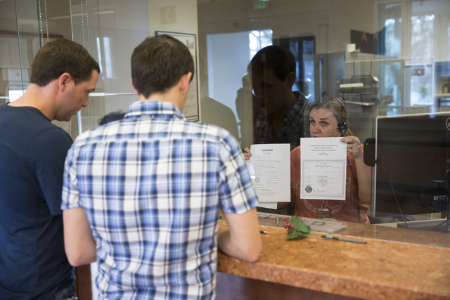 Greg Anderson, from left, and Chad Swiney of Tennessee complete their marriage license with office specialist Karen Stuart at the Clark County Marriage License Bureau on Friday, Jan. 13, 2017, in  ...