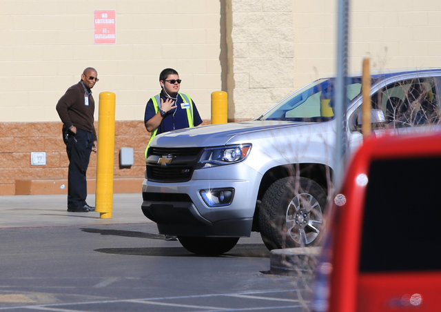 A Wal-Mart employee motions to a motorist that the store on East Serene Avenue is closed after a grease fire at the McDonald's inside closed down the store on Saturday, Jan. 28, 2017, in Las Vegas ...