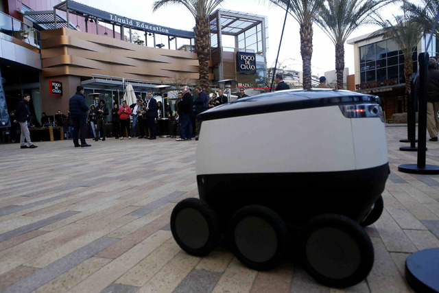 Guests watch a live demonstration in Downtown Summerlin, Wednesday, Jan. 04, 2017, in Las Vegas. The demonstration showed how through the collaboration of vans and robots, consumers could receive  ...