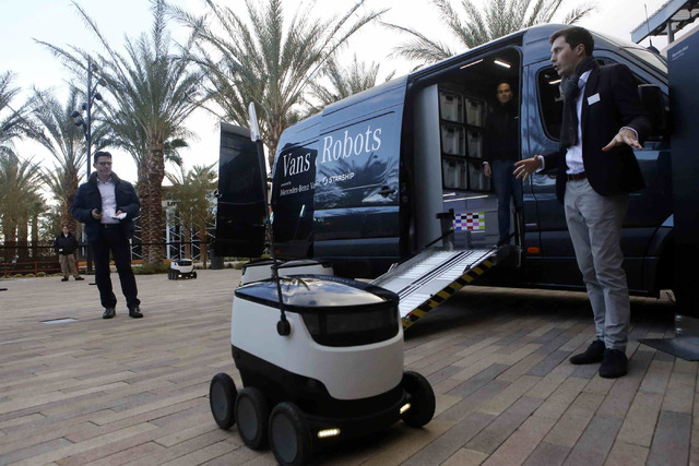 Spectators demonstrate how through the collaboration of vans and robots, consumers could receive packages to their house more efficiently in Downtown Summerlin, Wednesday, Jan. 04, 2017, in Las Ve ...