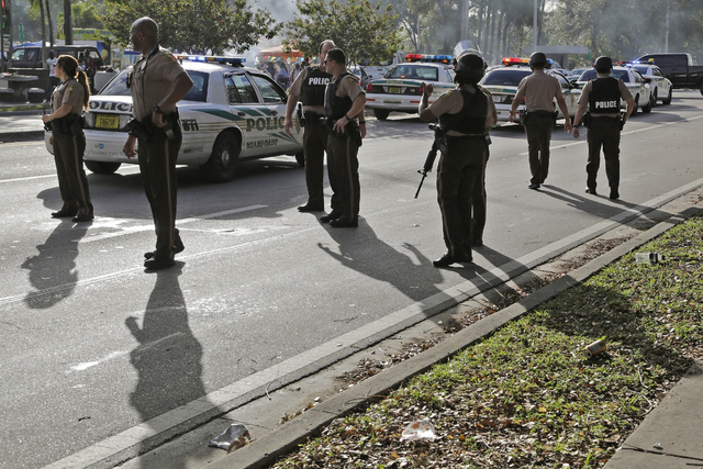 Miami-Dade Police secure the scene after several were injured in a shooting at Martin Luther King Jr. Memorial Park in Miami-Dade, Fla., Monday, Jan. 16, 2017. The Miami Herald reports that hundre ...